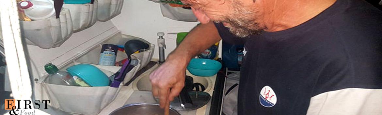 Chi cucina in barca a vela durante una crociera.